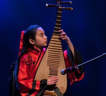 International Festival Photo of Angela Bolon on stage playing Pipa